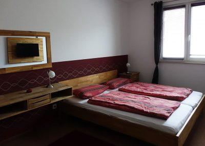 Schlafzimmer mit Doppelbett mit Fernseher